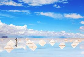 image of triangular pyramids  - Worker performing harvesting salt on the salt lake Salar de Uyuni, Bolivia ** Note: Shallow depth of field - JPG