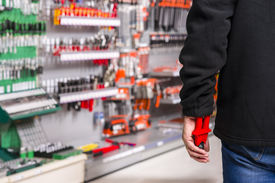 image of shoplifting  - male shoplifter stealing tools in a hardware store - JPG