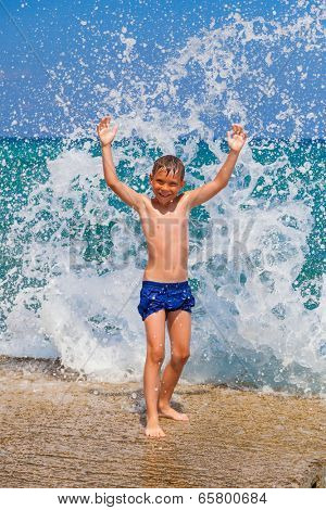 Little boy on the beach with big splashes on background