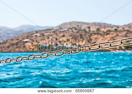 Steel Chain on the Sailing Boat with Coast at Background.