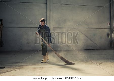 Worker cleaning an empty warehouse