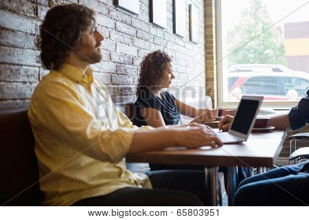 Male and female customers spending leisure time in coffeeshop