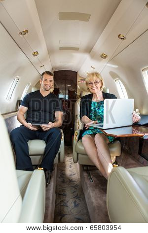 Portrait of confident business people with laptop and digital tablet in corporate jet