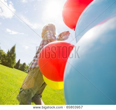 Young boy with helium balloons walking in green meadow