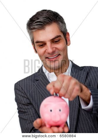 Assertive Businessman Saving Money In A Piggybank