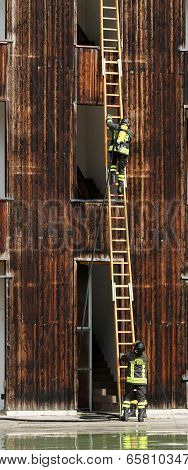Firefighters With Ladder During A Practice Session In The Firehouse