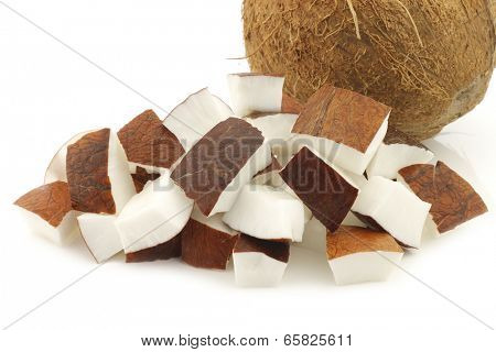 coconut and some cut pieces on a white background