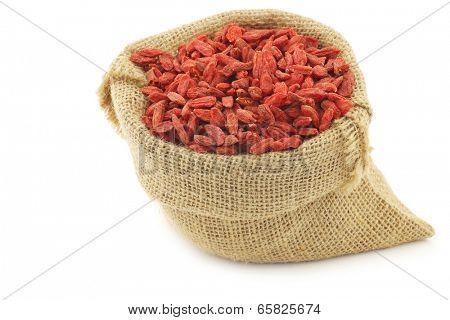 dried goji berries (Lycium Barbarum - Wolfberry) in a burlap bag on white background