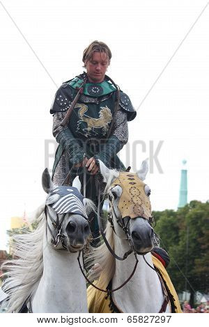 Riga, Latvia - August 21: Unidentified Man From The Devils Horsemen Stunt Team Riding Two White Hors