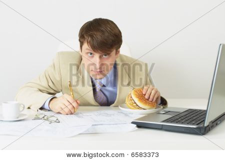 Person With The Big Sandwich In Hand Sits On A Workplace