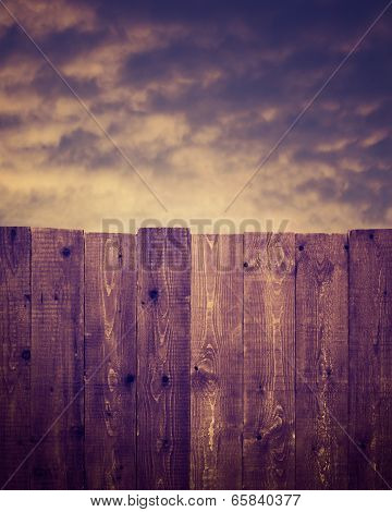 Wooden fence and cloudy sky