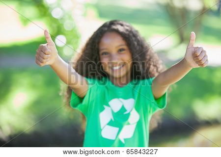Young environmental activist smiling at the camera showing thumbs up on a sunny day