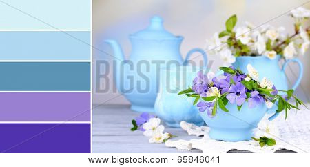 Beautiful spring flowers in cups on wooden table. Color palette with complimentary swatches