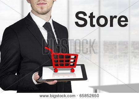 businessman holding tablet red cart