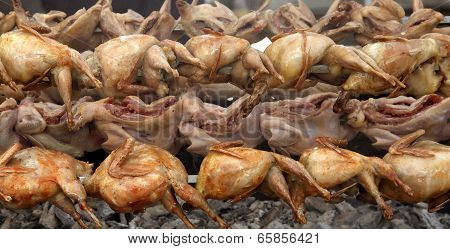 Quail Strung On A Skewer And Grilled In Barbecue