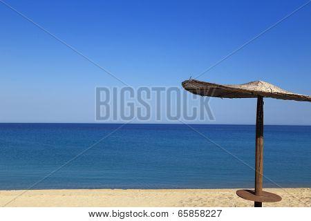 Sunny beach with wicker umbrella