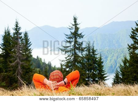 Hiker resting at viewpoint overlooking scenic mountains