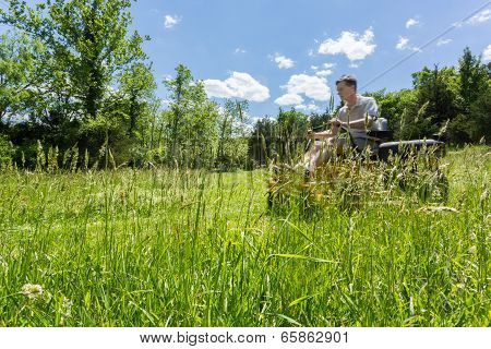 Senior Man On Zero Turn Lawnmower In Meadow