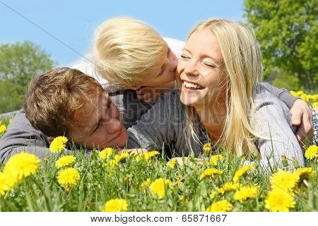 Mother, Father And Child Hugging And Kissing In Flower Meadow