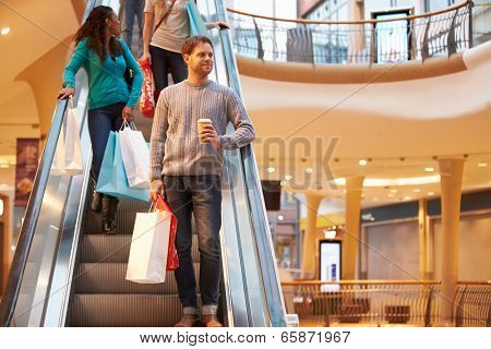 Male Shopper On Escalator In Shopping Mall