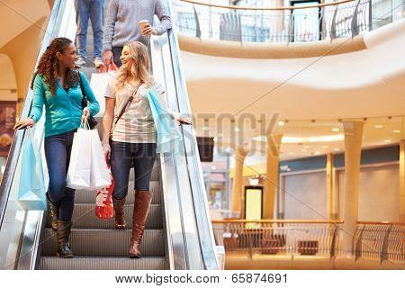 Two Female Friends On Escalator In Shopping Mall