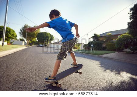 young boy learning to ride skateboard in the suburb street having fun.
