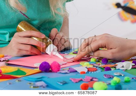 Woman Helping Girl In Making Cards