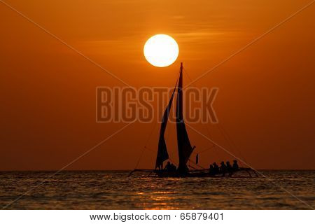 Sailing boat at sunset on sea