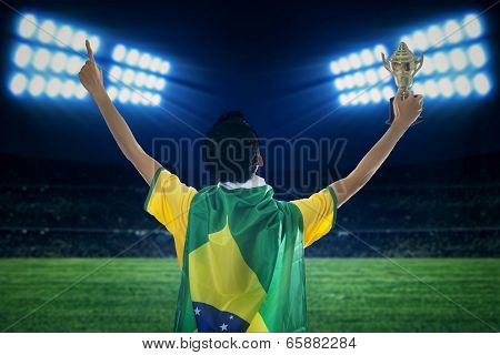 Soccer Player Holding Trophy At Field