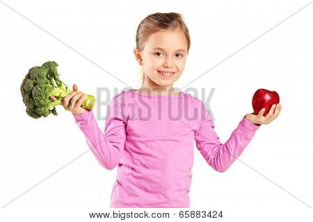Little girl holding a broccoli and an apple isolated on white background