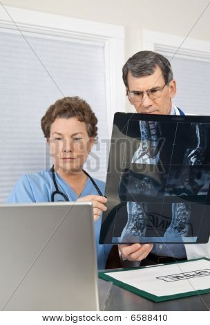 Doctor And Nurse Reading Spinal Mri Scan At The Computer