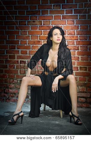 Charming young brunette woman in black and high heels near the brick wall. Sexy gorgeous young woman