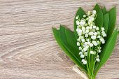 stock photo of lilly  - lilly of the valley flowers posy on wooden table with copy space - JPG