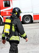foto of firehouse  - Italian firefighter with the oxygen cylinder and the helmet walks towards the fire - JPG