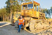 pic of heavy equipment operator  - positive driver of heavy equipment rests in the workplace - JPG