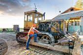 image of bulldozers  - working man in helmet examining bulldozer engine - JPG