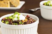 stock photo of kidney beans  - Vegetarian chili made with onions tomatoes corn kidney and black beans topped with sour cream and diced jalapeno served with cornbread - JPG