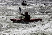 stock photo of rough-water  - silhouette of active male kayaker in rough water - JPG