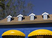 stock photo of awning  - yellow awning and blue windows with blue sky background - JPG