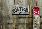 picture of log fence  - Rustic enter sign over barbed wire fence post with red barn birdhouse against rustic wooden background - JPG