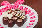 pic of truffle  - A variety of artisan chocolate truffles displayed on a white plate with a pink ribbon - JPG