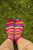 stock photo of peep toe  - Girl standing in the gras with her toe peeping out of multicolored striped socks - JPG