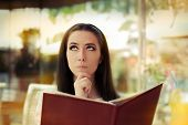 foto of restriction  - Young woman at a restaurant deciding what to order - JPG