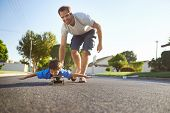 stock photo of skateboarding  - young boy learning to ride skateboard as father teaches him in the suburb street having fun - JPG