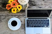 stock photo of keypad  - a cup of coffee and laptop on wooden tablewith flower - JPG