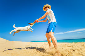 stock photo of frisbee  - dog catching a red frisbee with owner spinning around - JPG