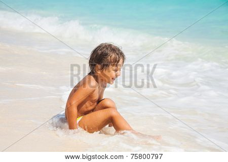 Happy boy sits on the sand beach with white waves