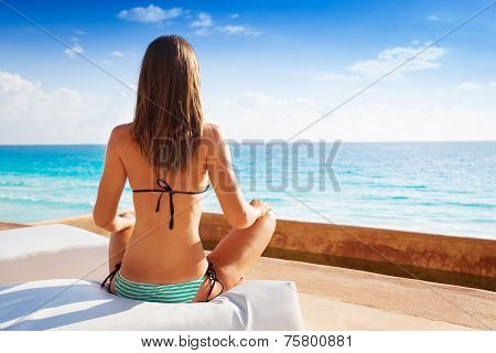Back of woman sitting in yoga position near sea
