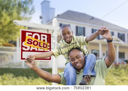 Happy African American Father and Son in Front of Home and Sold For Sale Real Estate Sign.