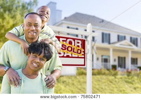 Happy African American Family In Front of Sold For Sale Real Estate Sign and House.